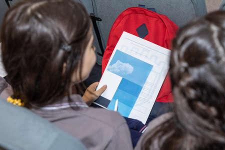 School girl holding a paper document top view 免版税图像