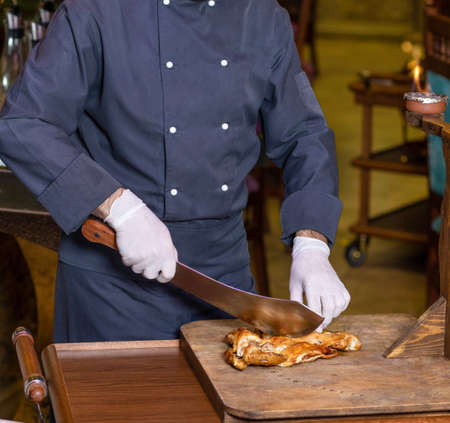 Chef cutting a chicken meat with a cleaver on the wood plate 免版税图像