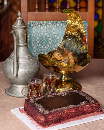 Arabic teapot glass and cake close up