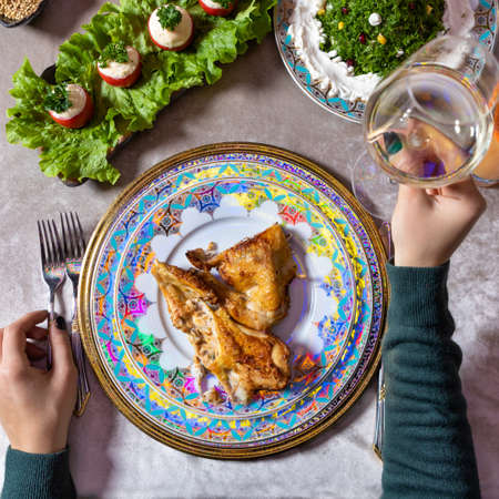 Woman holding a white wine, chicken meal on the table top view