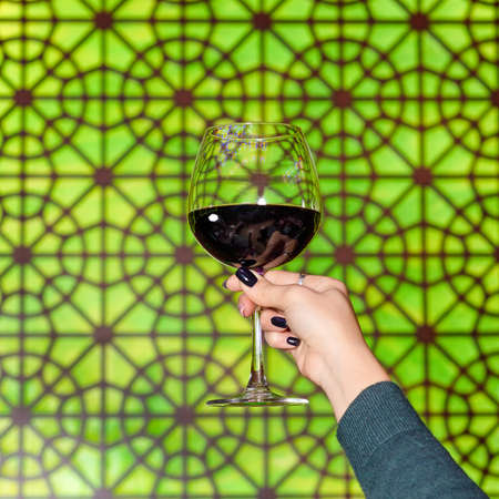 Woman holding a red wine glass with Arabic lantern background 免版税图像