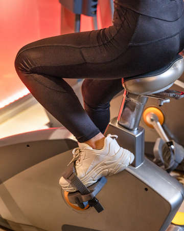 Cropped shot of fitness woman working out on exercise bike at the gym Banque d'images