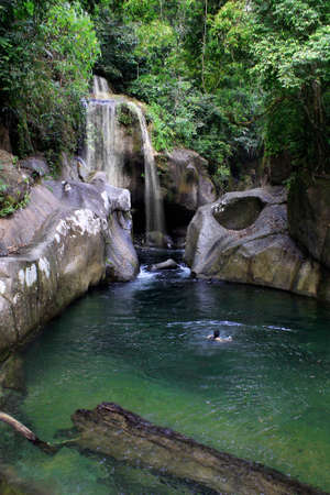 A boy swimming in a beautiful secret waterfall inside the jungle in West Sumatra