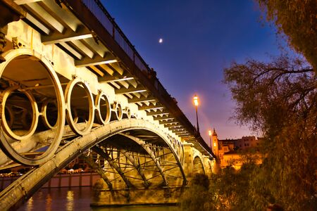Night photo of the Triana bridge with streetlights and reflections in the water, Seville,Andalusia, Spain. Archivio Fotografico