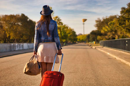 Young woman with a blue hat, denim jacket, skirt, red suitcase and brown bag walking on a road to start a journey or a new life, view from the back.