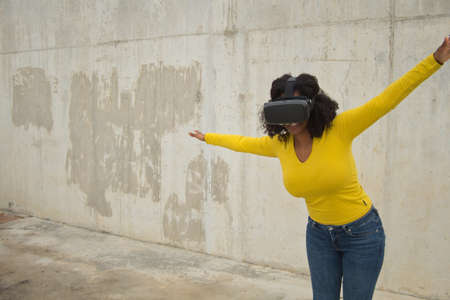 African american woman with afro hair and yellow t-shirt playing with virtual goggles on a concrete wall background.