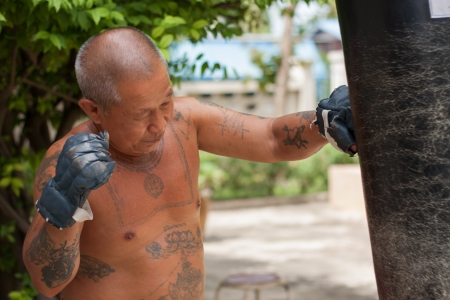 The old man practicing boxing, his body full of tattoo photo