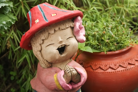 greet: Little clay doll girl smile and greet welcome ,thai style, wearing red hat and pink flower on ear