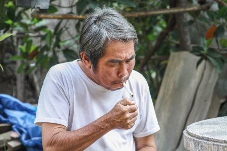 The old man lighting the cigarette at backyard photo