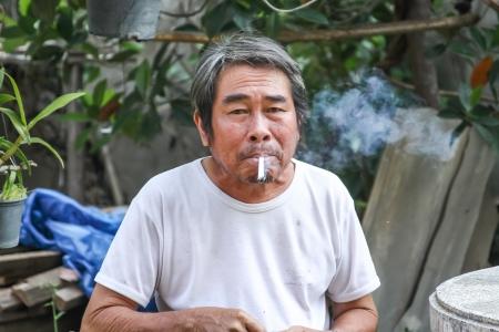 The old man are smoking at backyard photo