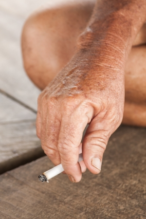asian old man: Hand of an asian old man holding a cigarette