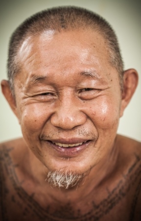 An asian old man happy face smiling and his body full of tattoo