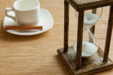 Hourglass on the Oak table as time passing concept for business deadline, urgency and running out of time.