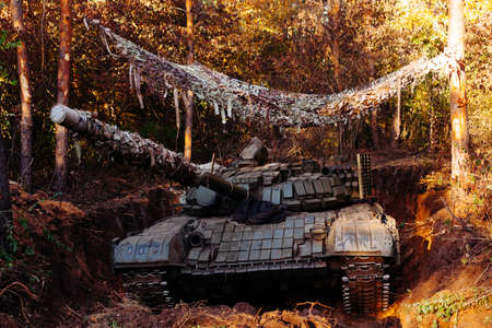 The tank from the hidden position is disguised in the trench Stock Photo