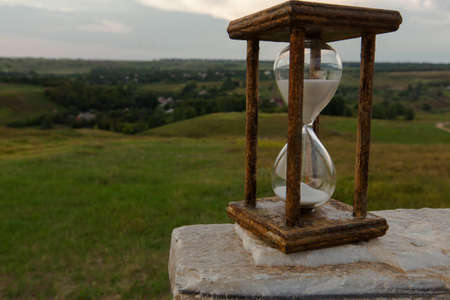 hourglass as a symbol of the passing time stand on a white stone marble Imagens