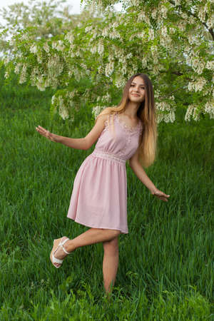 sexy girl with long hair and slender figure standing in green garden in spring