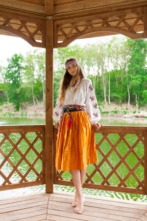 Beautiful slender Ukrainian in embroidery in windy weather enjoys a rest on the lake on a summer sunny day