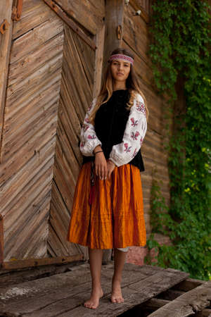 Beautiful Ukrainian woman dressed in embroidered rustic exteriors