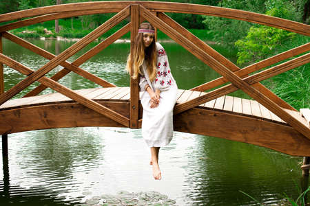 Beautiful slender Ukrainian in embroidery sits on the bridge over the water