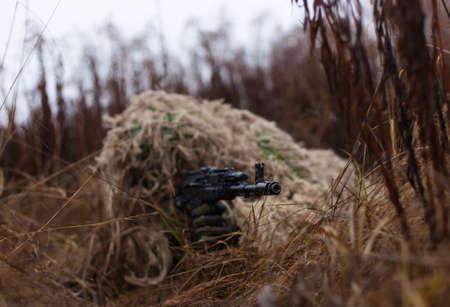 Ukraine modern soldier is ready to shoot a disguised kikimora 写真素材