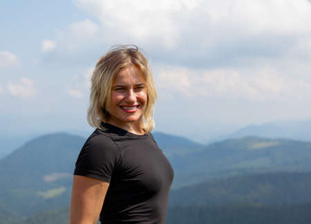 beautiful girl travels in a tight T-shirt high in the mountains