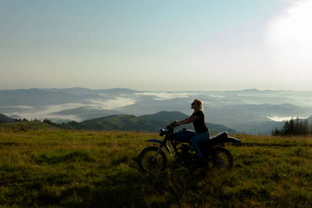 girl on a motorcycle high in the mountains stopped to rest at dawn travels