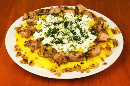 Kulesha, mamalyga, polenta with meat and homemade cheese on the plate, traditional Urkainian and Hutsul meal