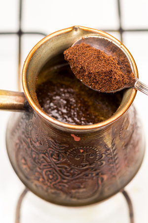 cezve: Turkish pot cezve and spoon with ground coffee, close-up, top view. Stock Photo