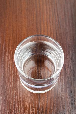 agua purificada: vaso lleno de agua purificada transparente sobre la mesa de madera, vista desde arriba