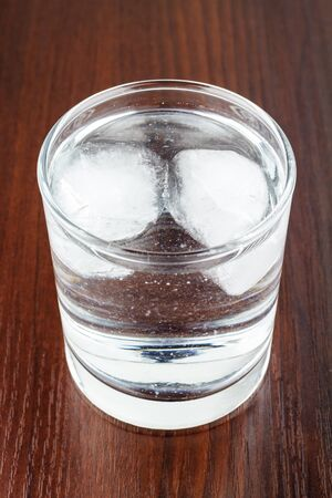 purified: Full glass of transparent purified water with ice on wooden table Stock Photo