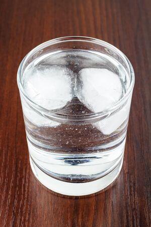 agua purificada: vaso lleno de agua purificada transparente con hielo en la mesa de madera Foto de archivo