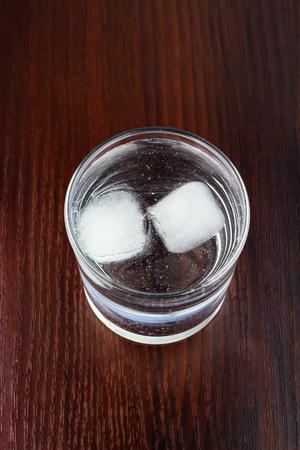 agua purificada: vaso lleno de agua purificada transparente con hielo en la mesa de madera, vista desde arriba