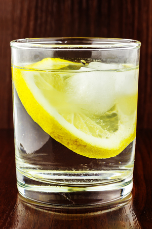 purified: Full glass of transparent purified water with slice of lemon and ice cube, on wooden table