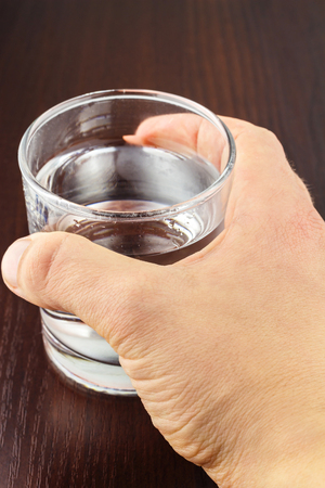 purified: Mens hand holding glass of transparent purified water on wooden table.