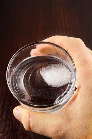 agua purificada: para hombre de la mano que sostiene el vidrio de agua purificada transparente con hielo en la mesa de madera, vista desde arriba