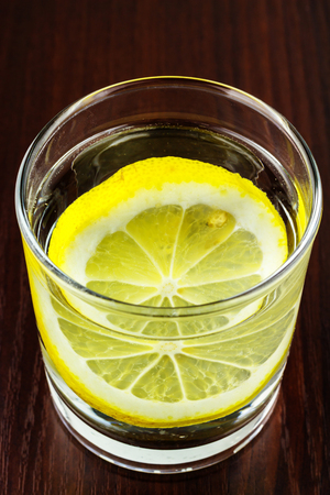 purified: Full glass of transparent purified water with slice of lemon, on wooden table