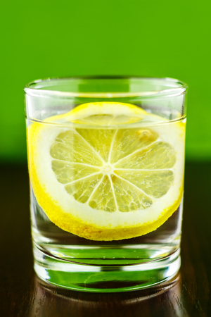 purified: Full glass of transparent purified water with slice of lemon, on wooden table and blurred green background