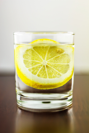 purified: Full glass of transparent purified water with slice of lemon, on wooden table, and blurred white background