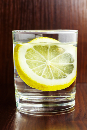 agua purificada: Full glass of transparent purified water with slice of lemon, on wooden table