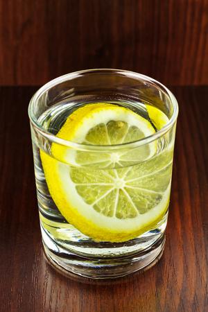 agua purificada: vaso lleno de agua purificada transparente con una rodaja de limón, en mesa de madera