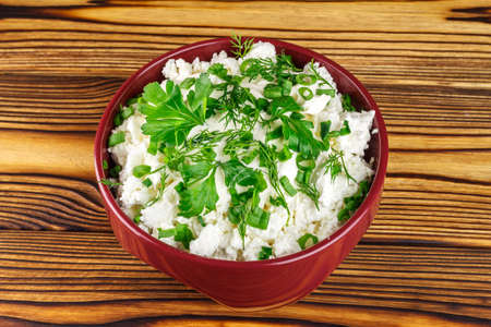 dill and parsley: Fresh and natural cottage cheese with sour cream, dill, parsley, onion in ceramic bowl on wooden table