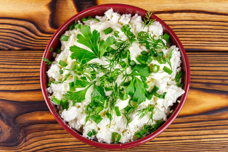 dill and parsley: Fresh and natural cottage cheese with sour cream, dill, parsley, onion in ceramic bowl on wooden table, top view