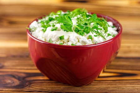 dill and parsley: Fresh and natural cottage cheese with sour cream, dill, parsley, onion in ceramic bowl on wooden table, selective focus Stock Photo