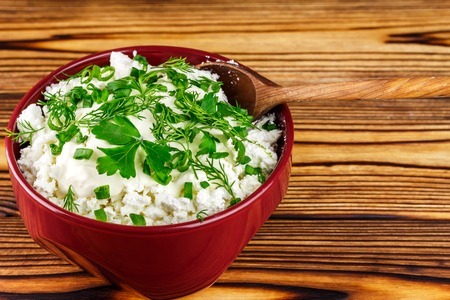 dill and parsley: Fresh and natural cottage cheese with sour cream, dill, parsley, onion and spoon in ceramic bowl on wooden table, space for text Stock Photo