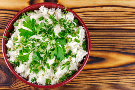 dill and parsley: Fresh and natural cottage cheese with sour cream, dill, parsley, onion in ceramic bowl on wooden table, top view, space for text