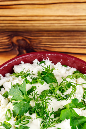 dill and parsley: Fresh and natural cottage cheese with sour cream, dill, parsley, onion in ceramic bowl on wooden table,  top view, space for text Stock Photo