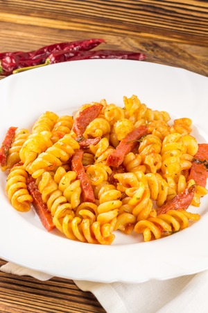 a portion: Italian pasta fusilli with tomato sauce and sausage in plate, napkin, pepper on wooden table. Stock Photo