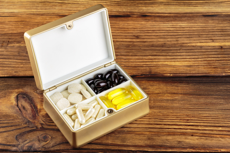 food supplement: Mixed natural food supplement pills in container, omega 3, vitamin c, carotene capsules, on wooden background
