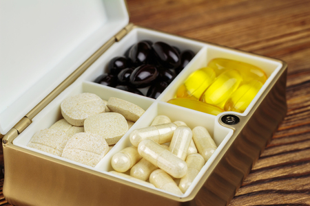 food supplement: Mixed natural food supplement pills in container, omega 3, vitamin c, carotene capsules, on wooden background, selective focus Stock Photo