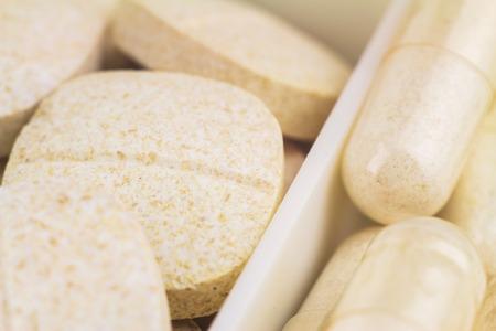 food supplement: Mixed natural food supplement pills, vitamin c, glucosamine capsules, macro image, selective focus Stock Photo